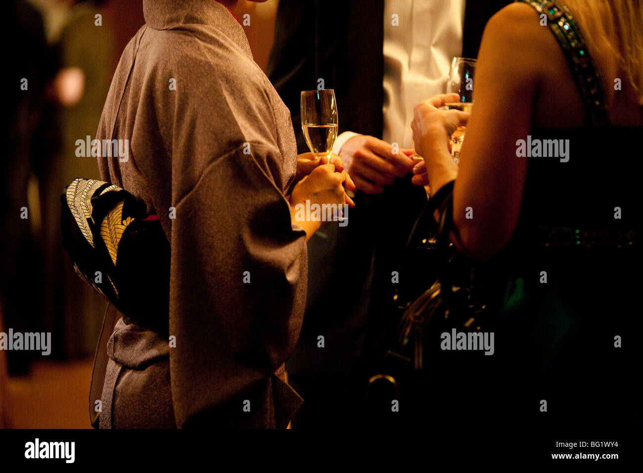 Japanese woman in kimono drinking champagne with Woman in Western style dress, and man in black tie.. - Stock Image