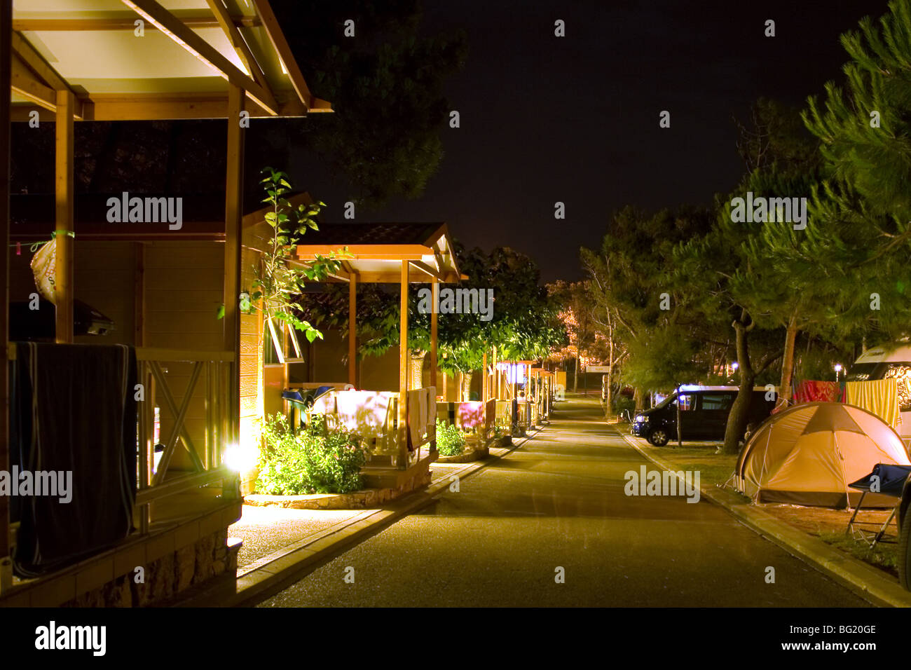 Summer night shot of log cabins on campsite - Stock Image