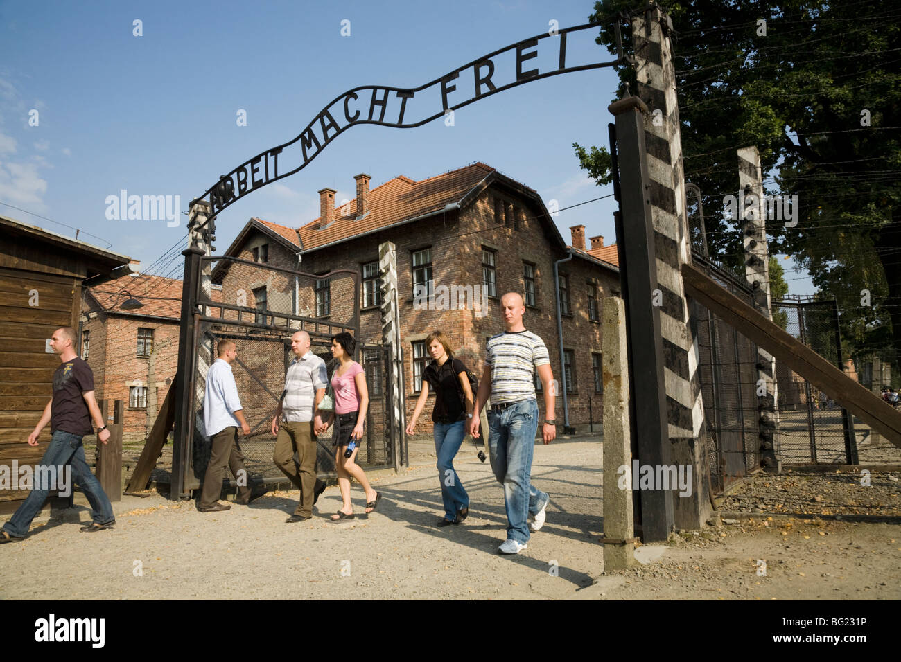 Tourists at the main entrance – with REAL Arbeit Macht Frei slogan above the gates – at Auschwitz Nazi camp in Oswiecim, - Stock Image