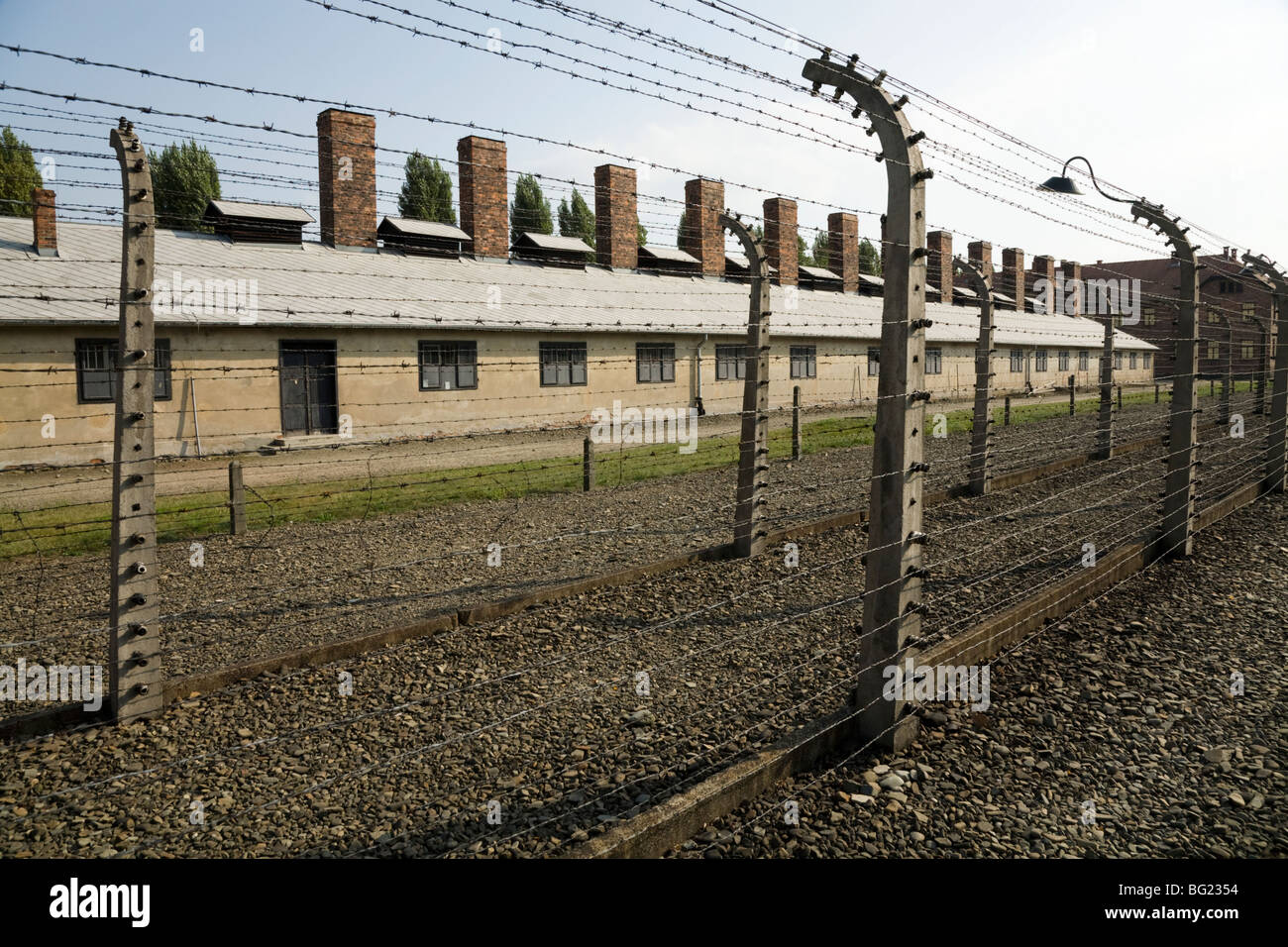 Perimeter electric fence at Auschwitz Nazi death camp in Oswiecim, Poland. Chimneys from the kitchen block are visible - Stock Image
