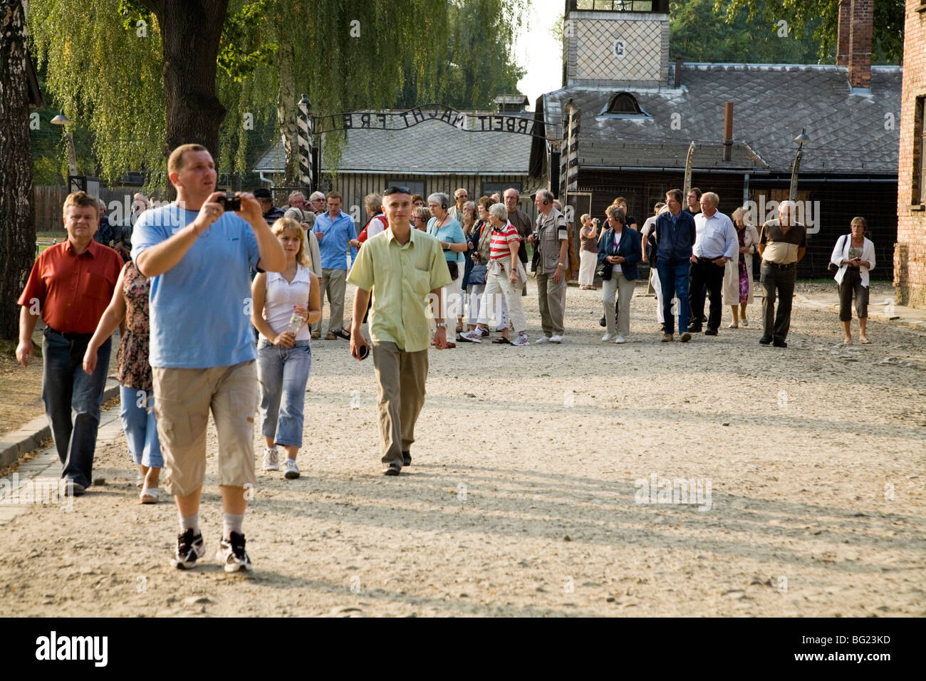 Tourists view Auschwitz Nazi death camp. The main entrance – with slogan 'Arbeit Macht Frei' – is above - Stock Image