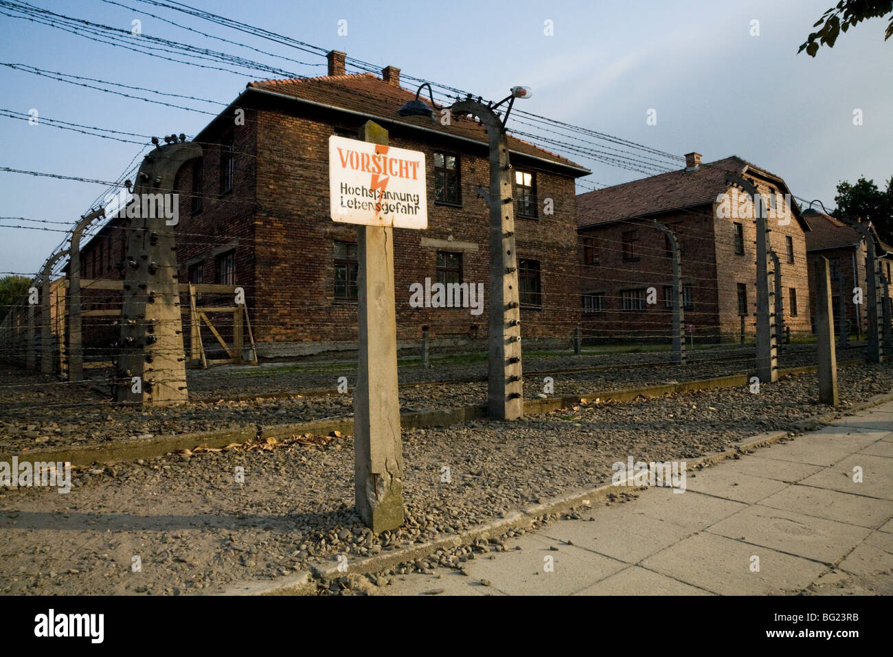 Perimeter electric fence & warning sign at Auschwitz Nazi death camp. Oswiecim, Poland. Prisoner accommodation - Stock Image