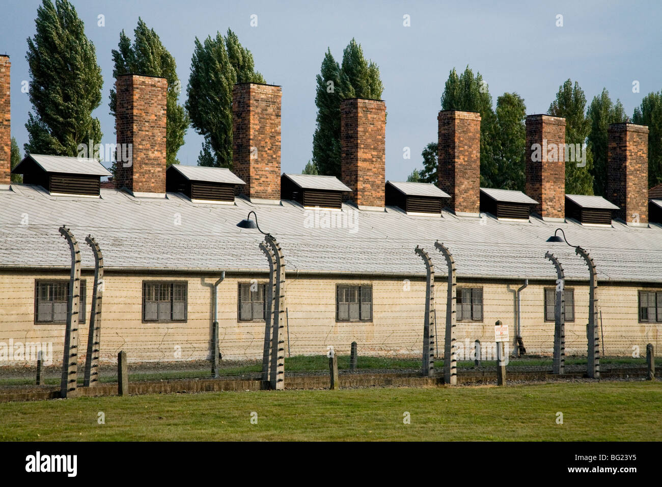 Perimeter electric fence at Auschwitz Nazi death camp, with catering block and kitchen chimneys behind. Oswiecim, - Stock Image