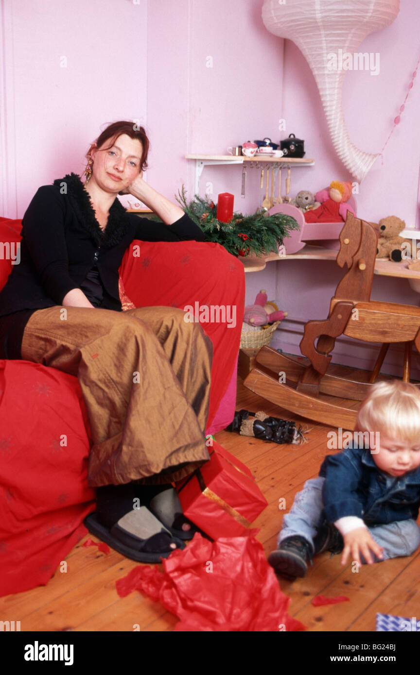 Exhausted single mum with Christmas at home sit on sofa  SerieCVS117002 - Stock Image