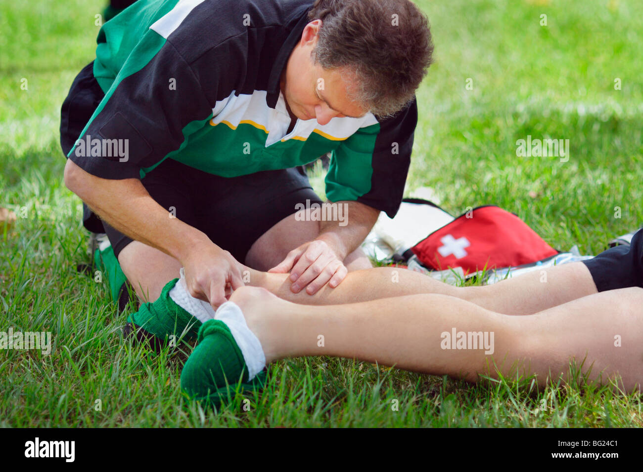 Man administering first aid to person's ankle - Stock Image