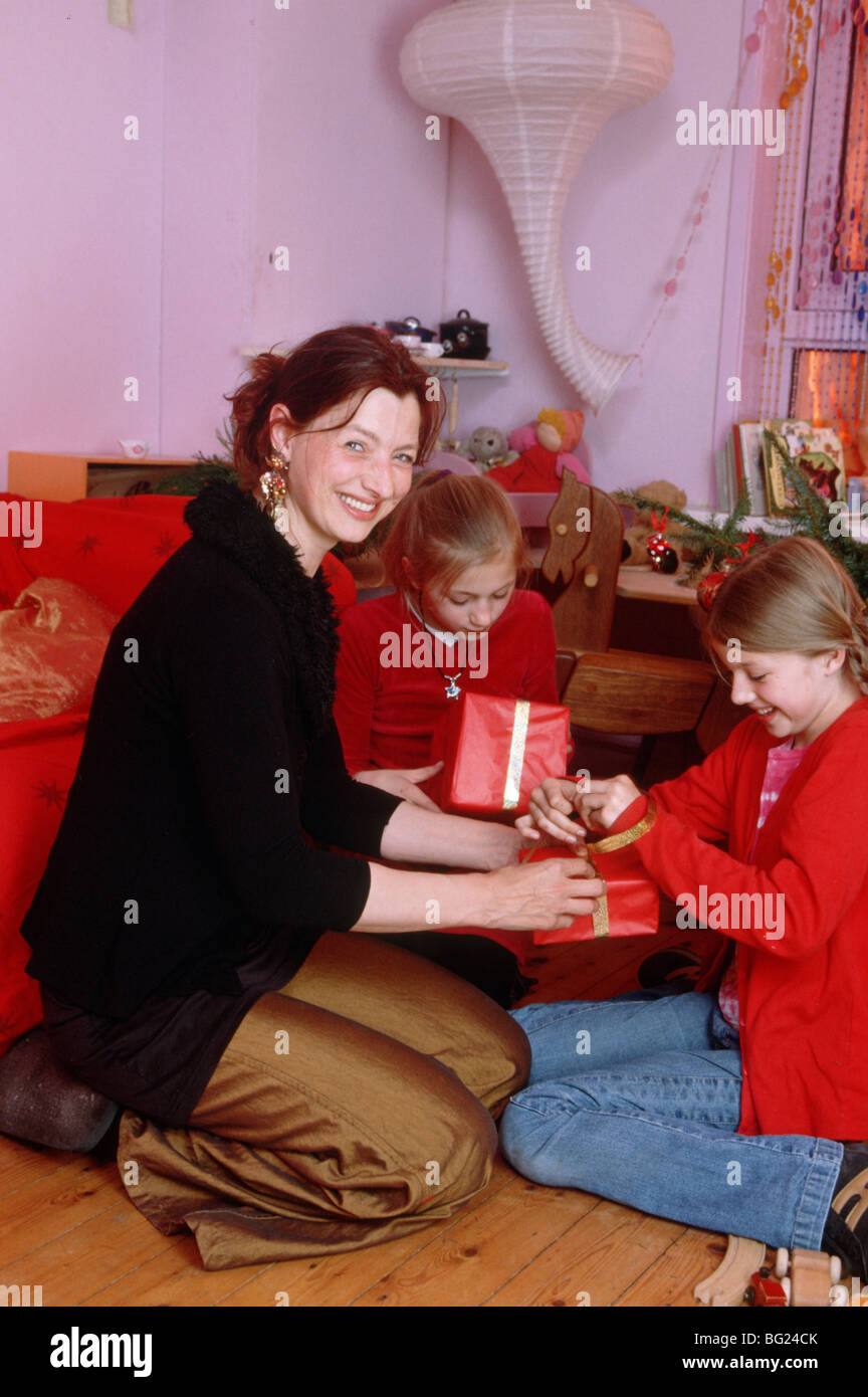 Mother and preteen girls unwrapping christmas gifts at home SerieCVS117002 - Stock Image