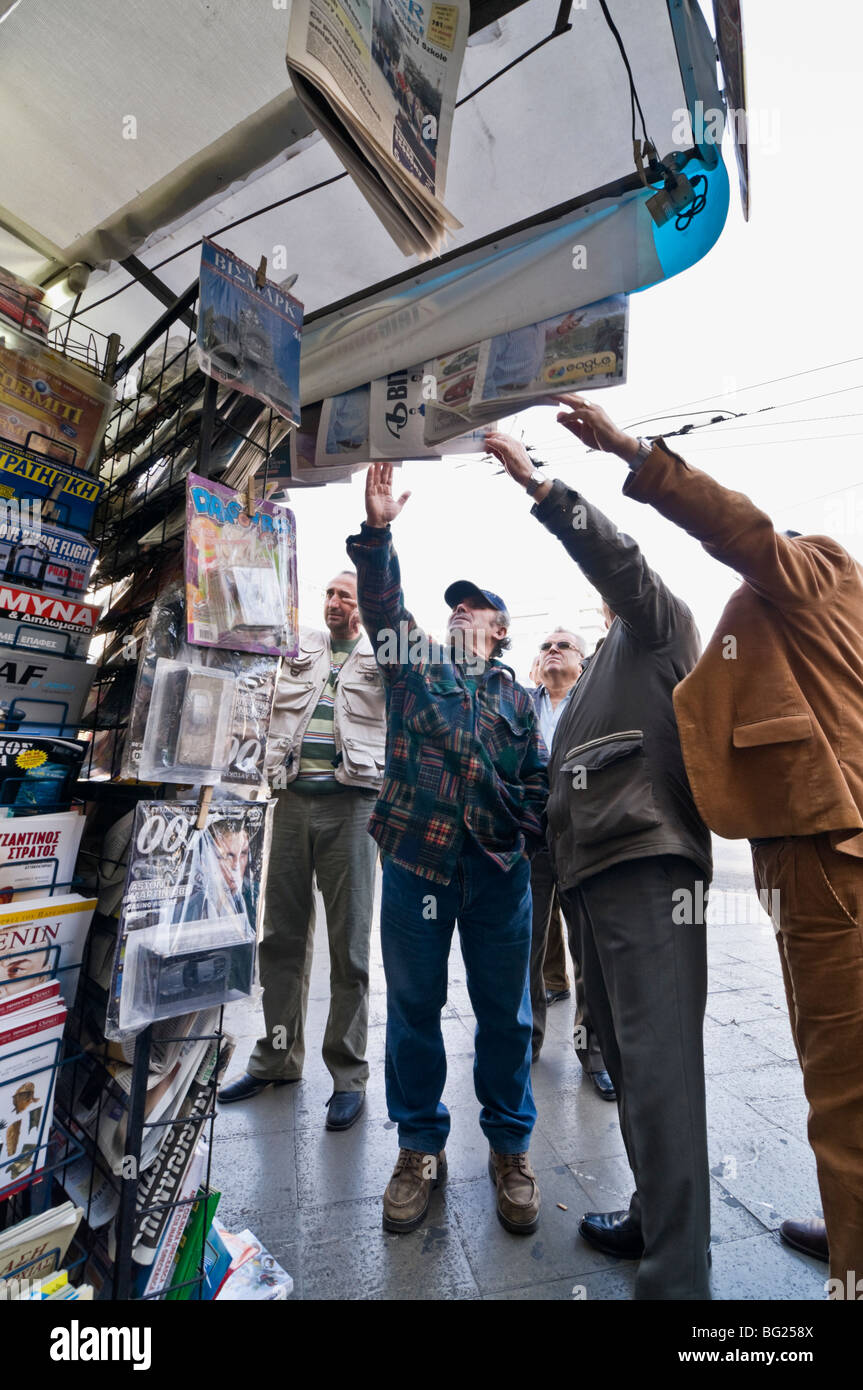 Reading the headlines on newspapers displayed above a periptero (news kiosk) in Omonia Square in the centre of Athens, - Stock Image