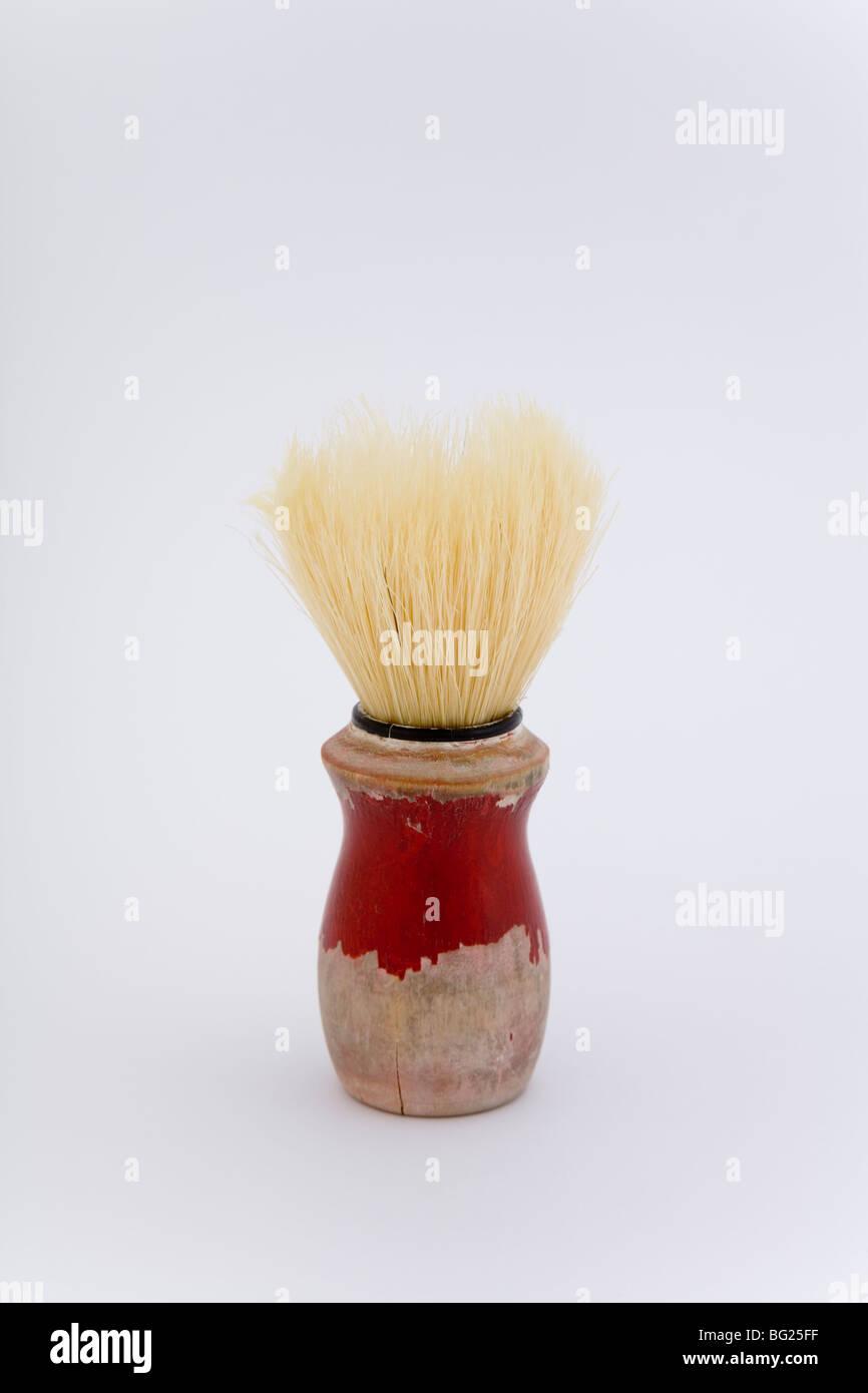 One red worn old shaving brush male man shave accessory manhood habit beard daily white background old use used - Stock Image