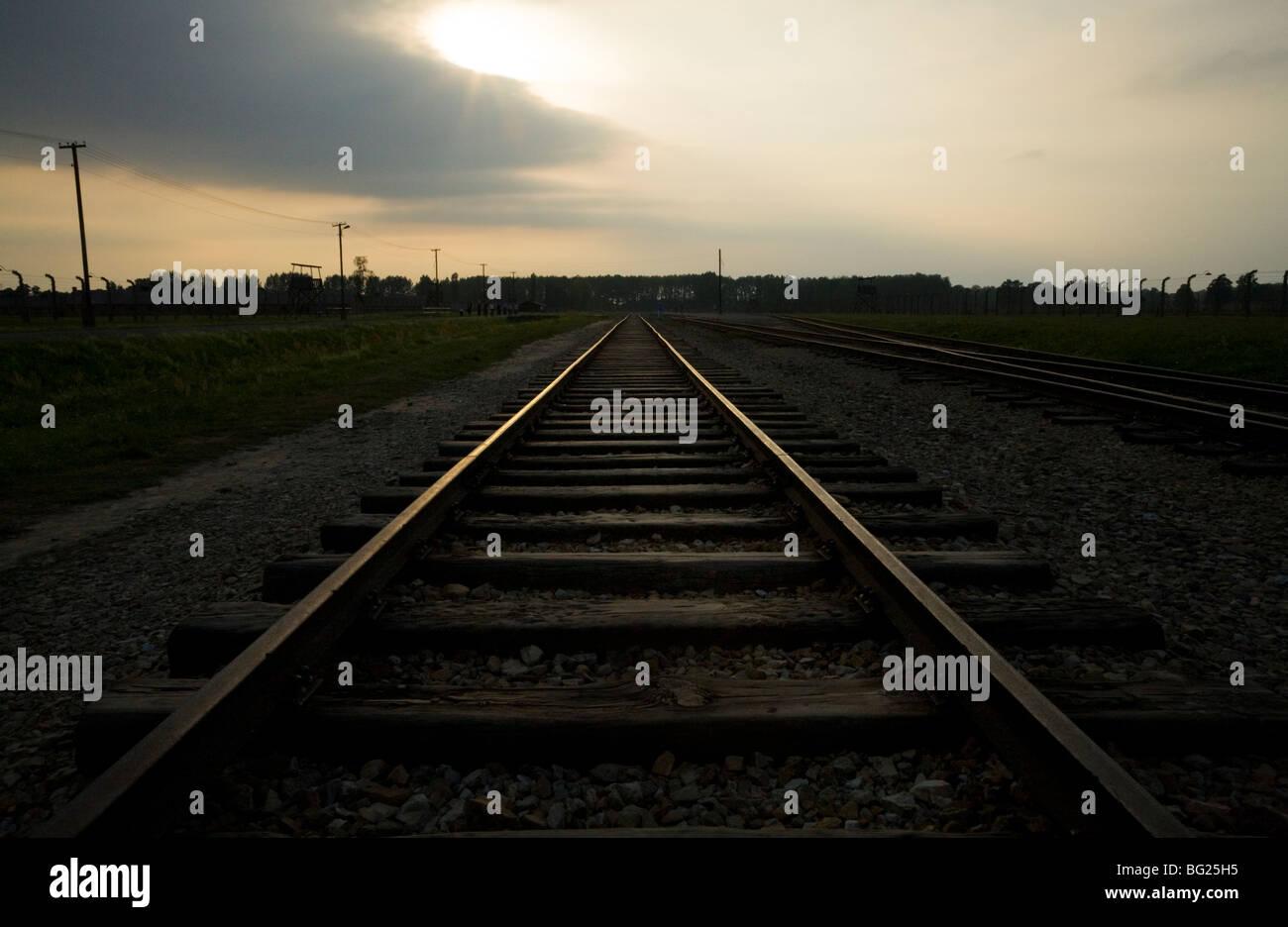 Railway lines at dusk inside Birkenau (Auschwitz II - Birkenau) Nazi concentration camp in Oswiecim, Poland. - Stock Image