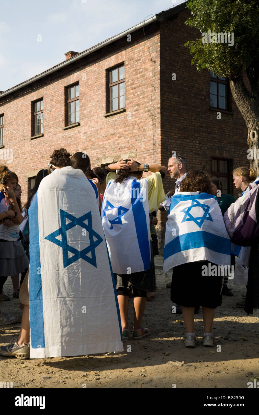 Jewish school / college children / students: group on a tour of Auschwitz Nazi camp. Poland. Girls are wearing Israeli - Stock Image