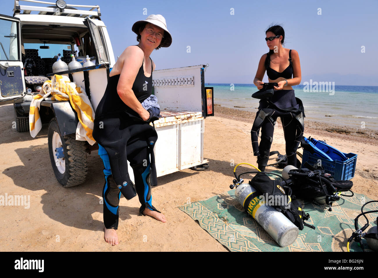 "Two woman scuba divers prepare on beach for a shore dive, Nuweiba, ""Red Sea"", Egypt Stock Photo"