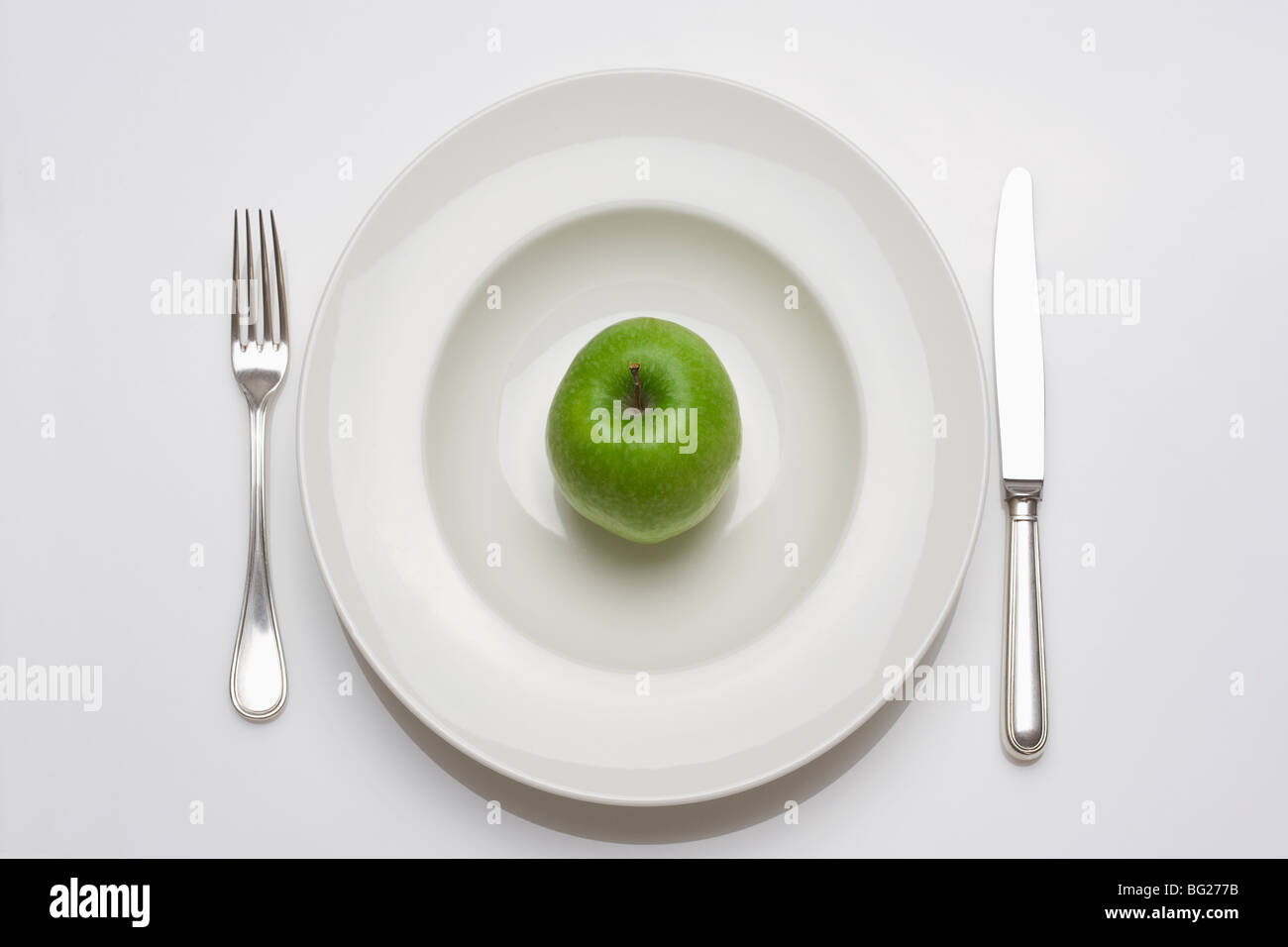 diet - green apple on a white plate with knife and fork - Stock Image