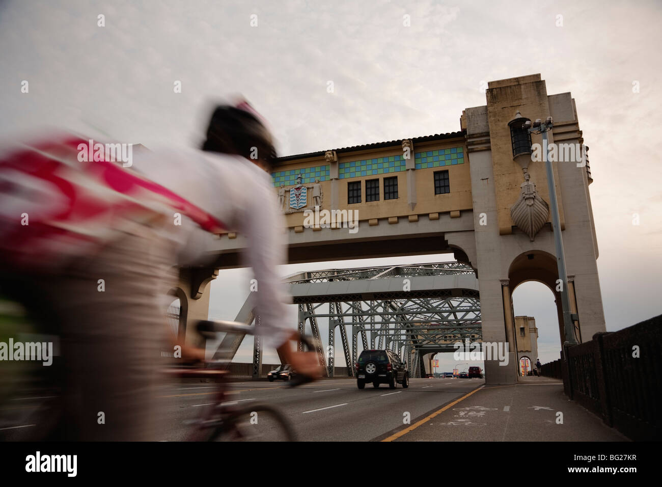 Bicyclist speeds by on the bike lane on Burrard Street Bridge, Vancouver, BC, Canada - Stock Image