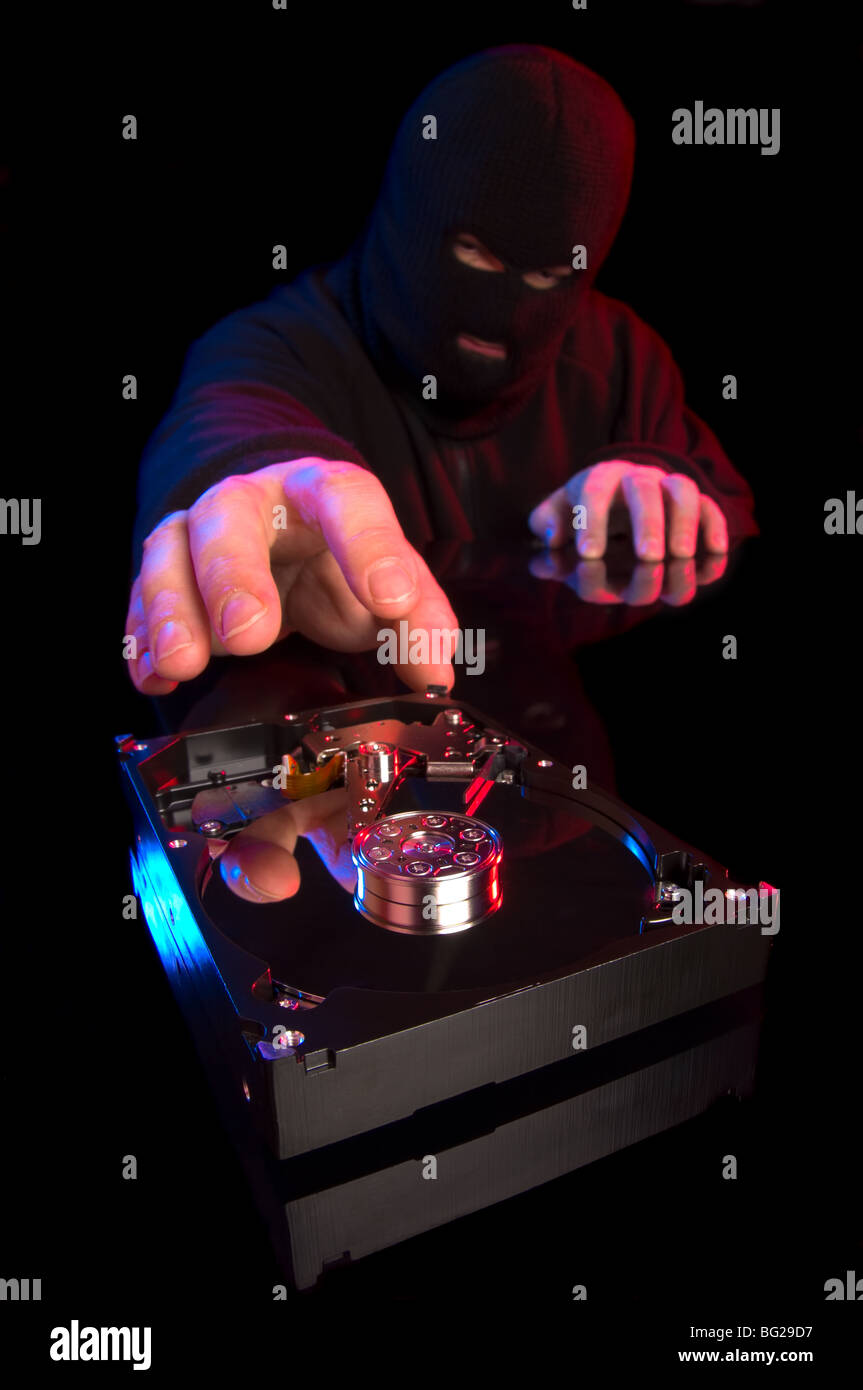 Concept of data theft with hooded thief stealing computer information stored in hard drive - Stock Image