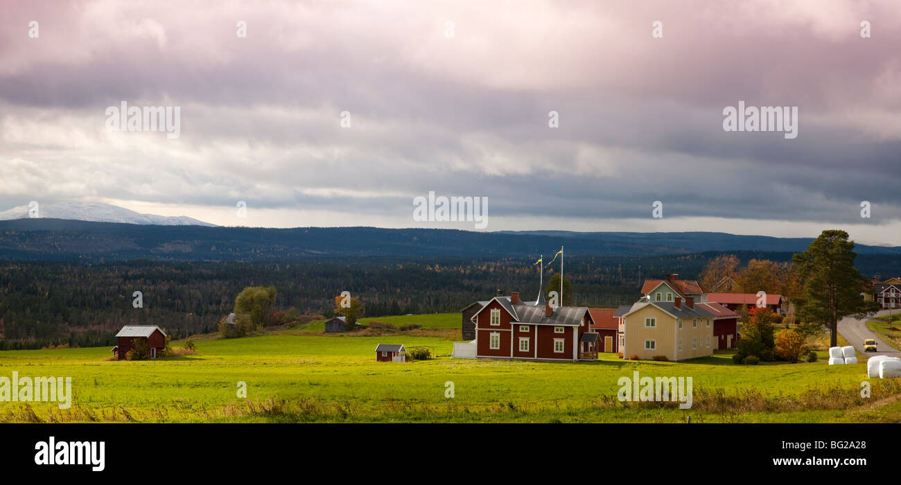 View over traditional farm with swedish flags and forest and fjells with first snow Jämtland Sweden in autumn with Stock Photo