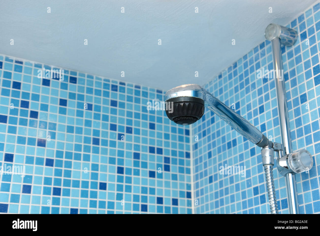 Shower Head In Bathroom Of Blue Mosaic Tiles Stock Photo