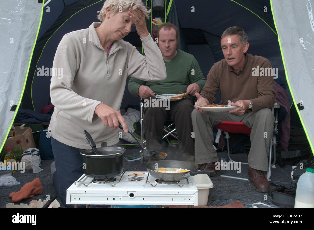 woman in tent cooking for two men as they just watch, Lazy men. - Stock Image