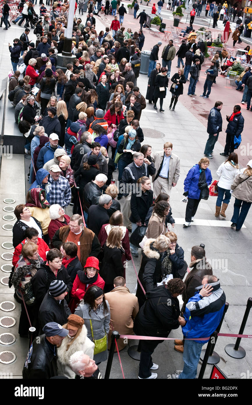 TKTS packed coiled queue for half price Broadway tickets in Times Square pedestrian mall during Christmas season - Stock Image