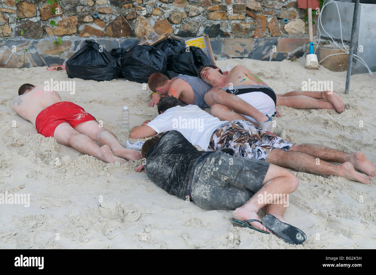 people asleep on the beach after full moon party haad Rin Koh Phangan Thailand - Stock Image