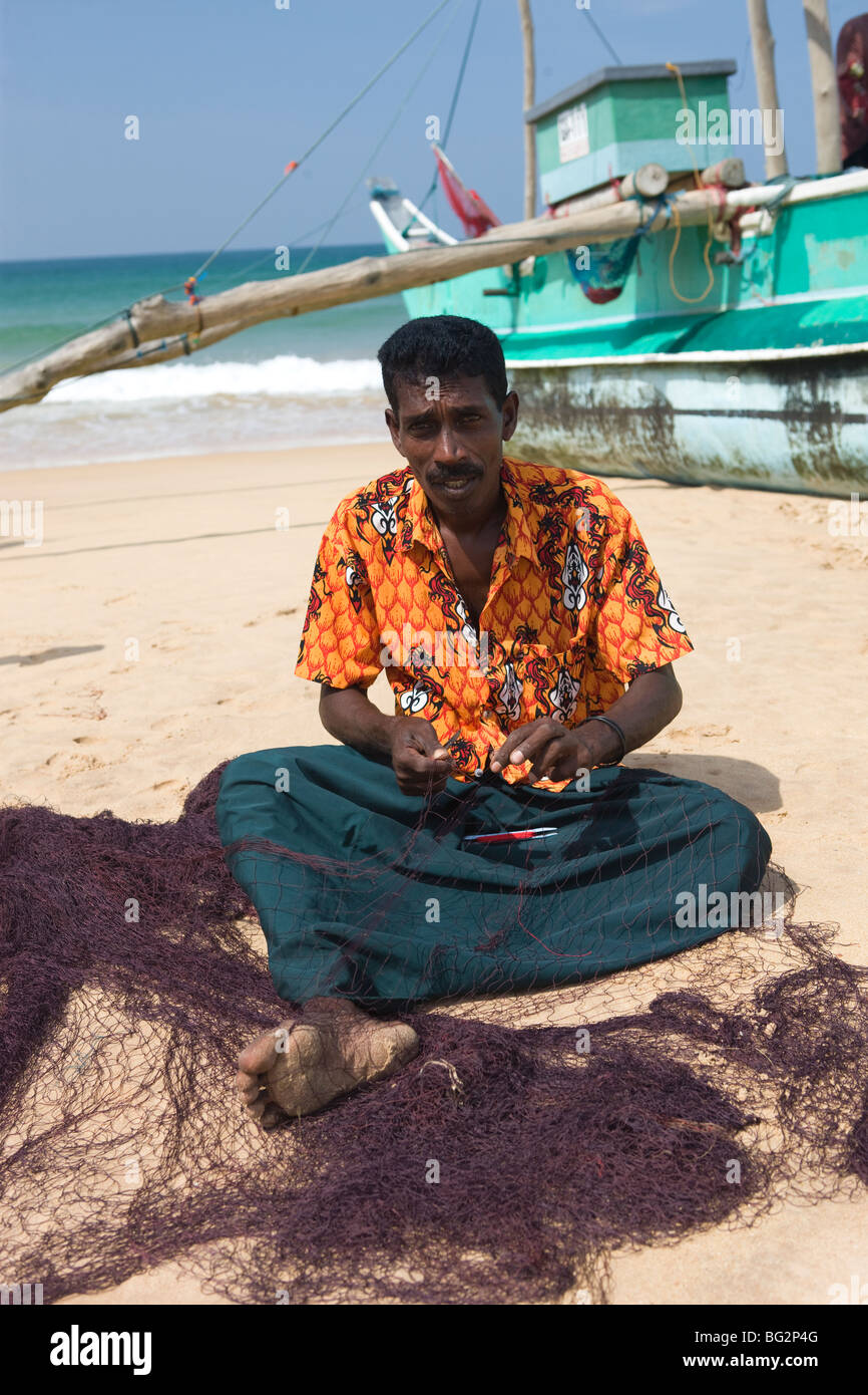 Fisherman repairing the nets, Hikkaduwa, Sri Lanka - Stock Image