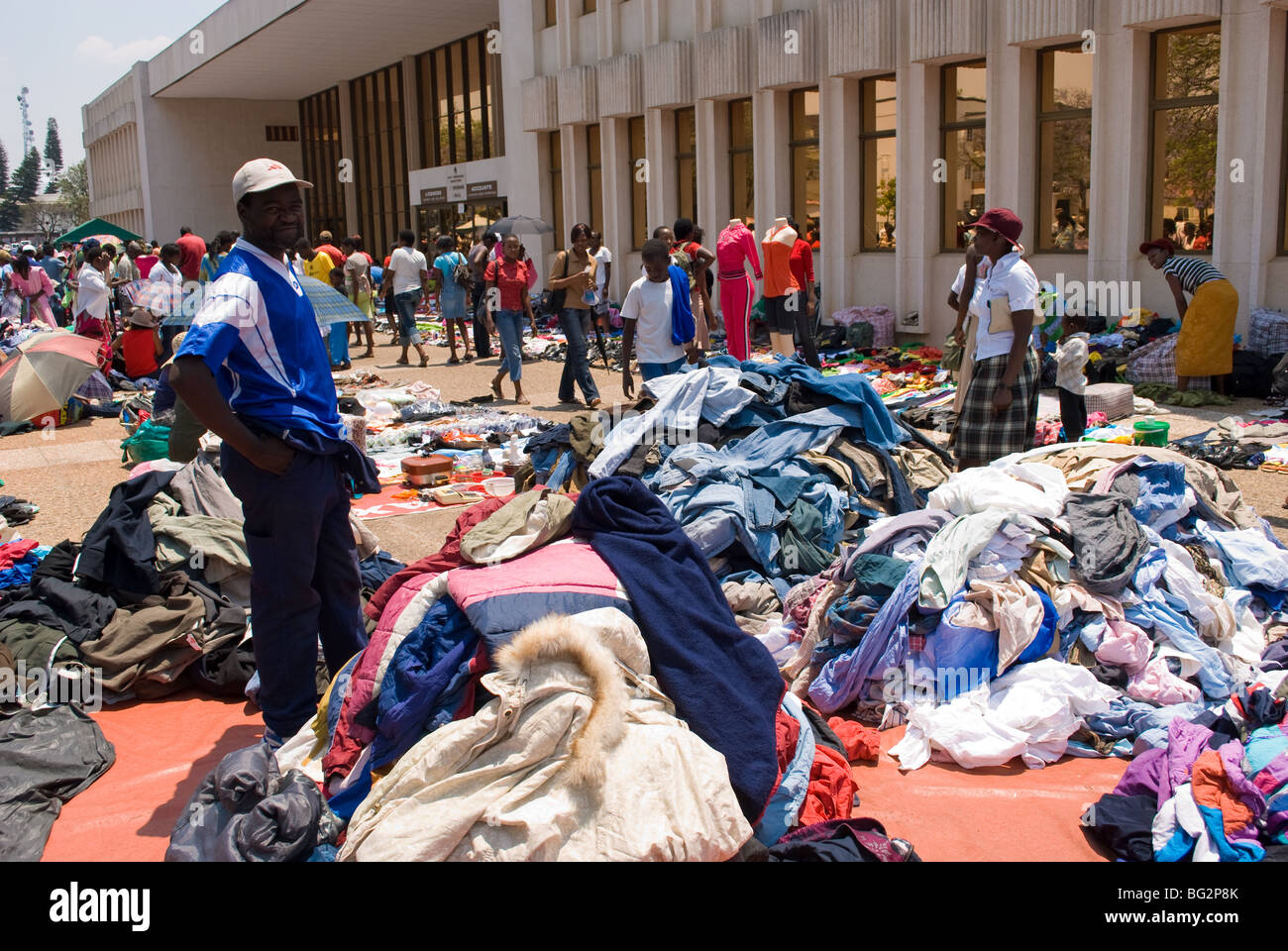 A vendor surveys mountains of second hand clothing for sale at the ...