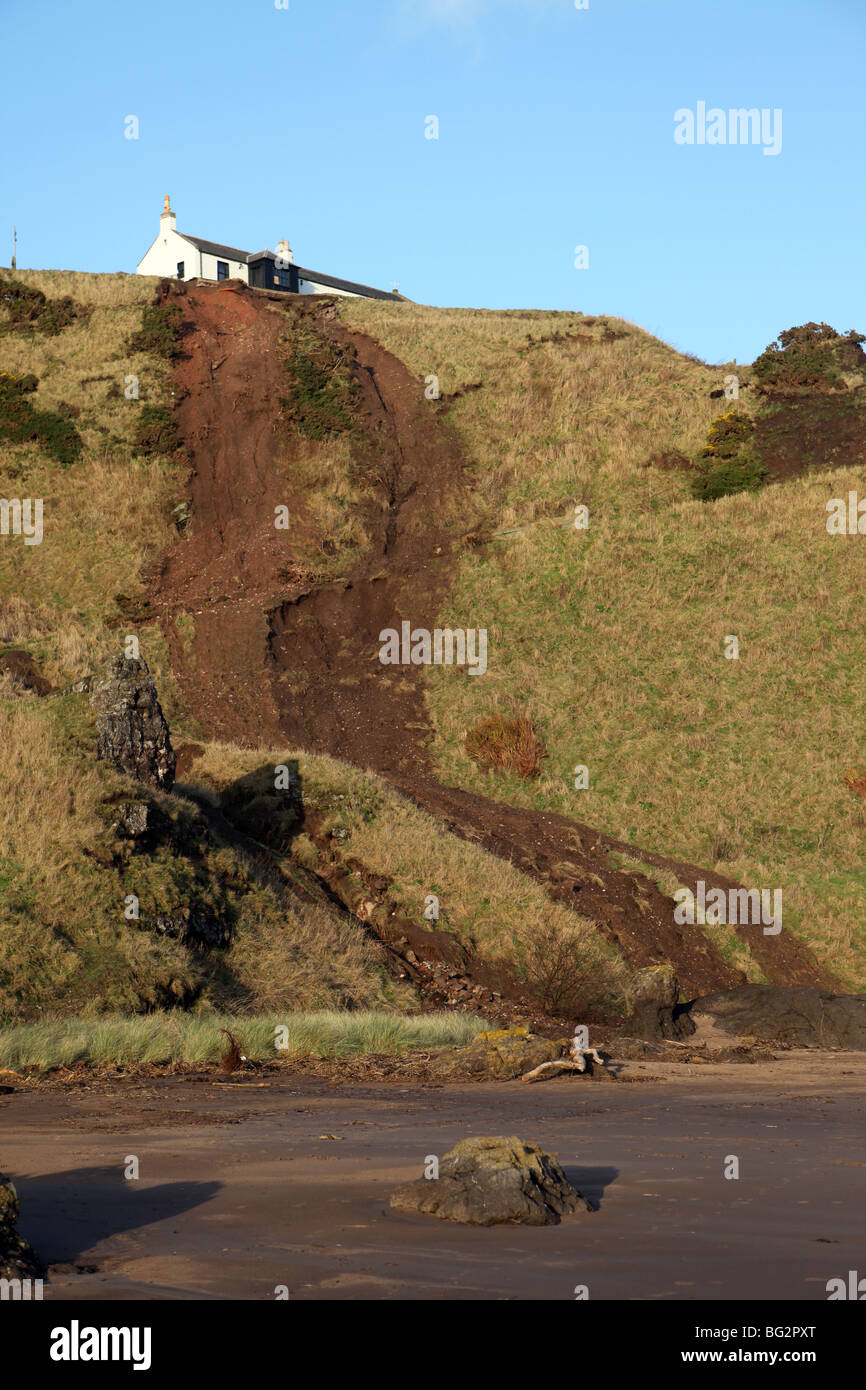 House on top of cliffs with after effects of a mud slide after storm and heavy rain at St Cyrus, Scotland, Uk - Stock Image