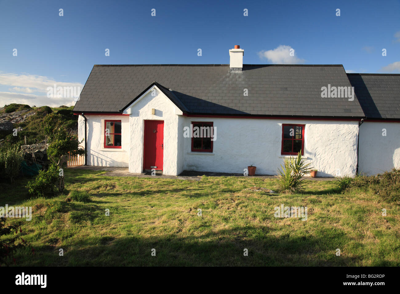 summer cottage with red door and windows in Ballyconneely near Roundstone, Connemara, Ireland - Stock Image