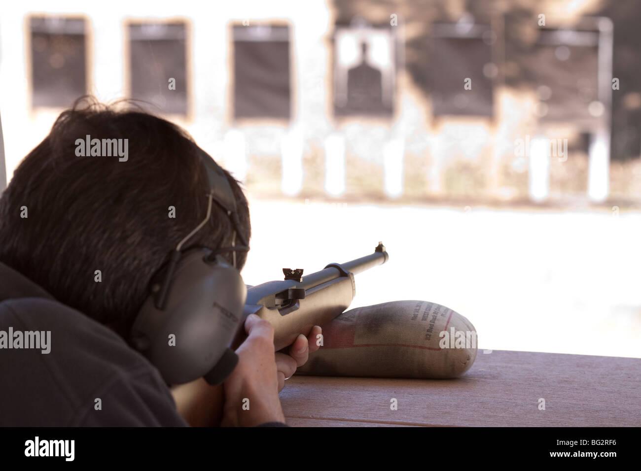 Man aiming Ruger 10/22 rifle at targets at Los Altos Rod and Gun Club outdoor gun range - Stock Image
