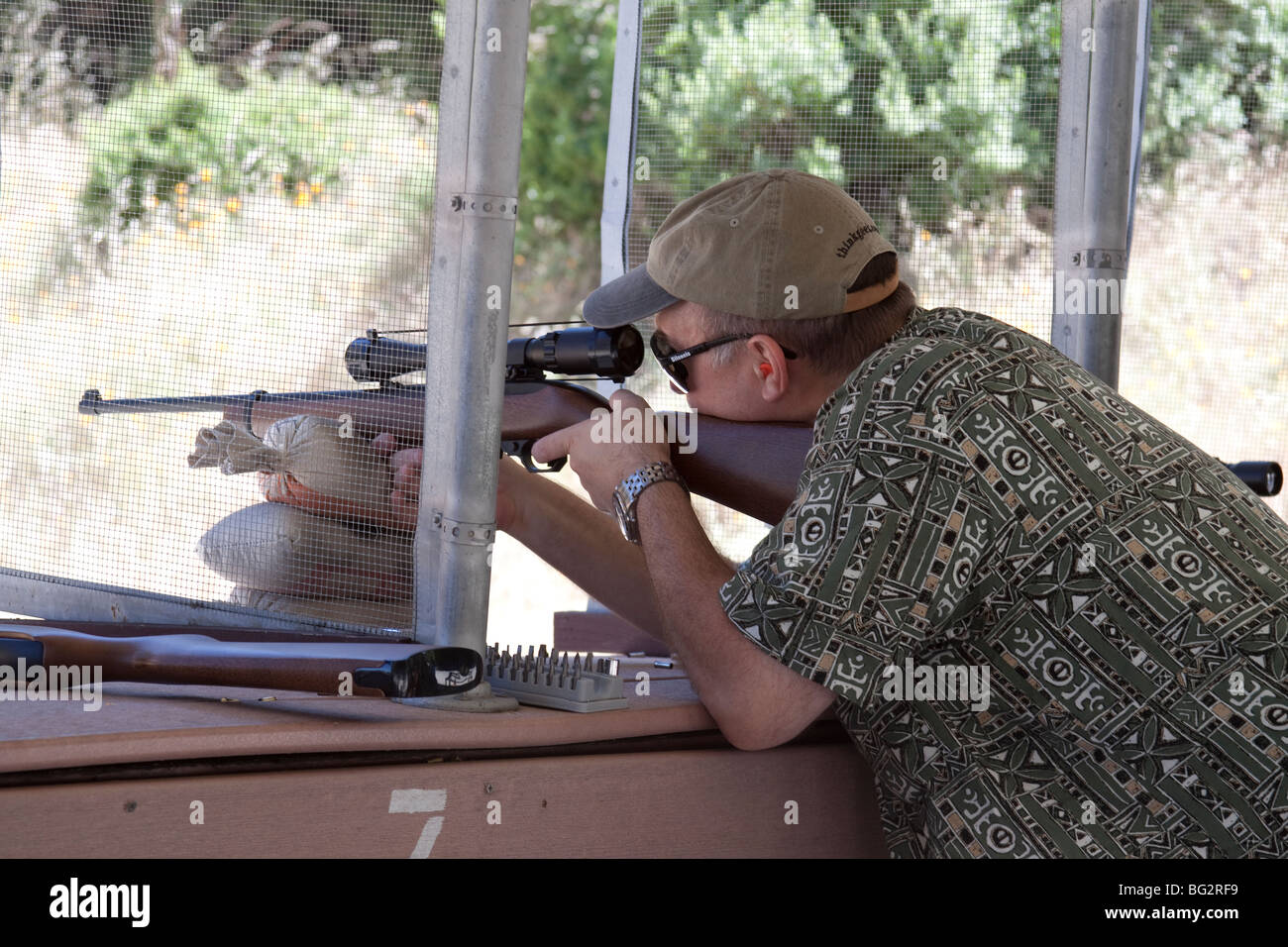 Man resting Ruger 10/22 rifle on sandbags as he practices target shooting at the Los Altos Rod and Gun Club outdoor - Stock Image