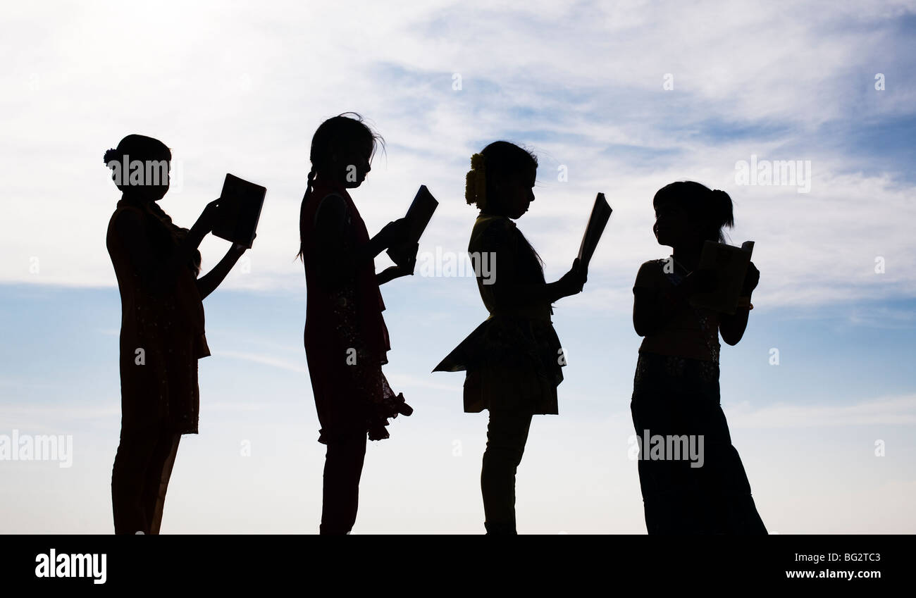Silhouette of Indian girls reading books standing in a line - Stock Image