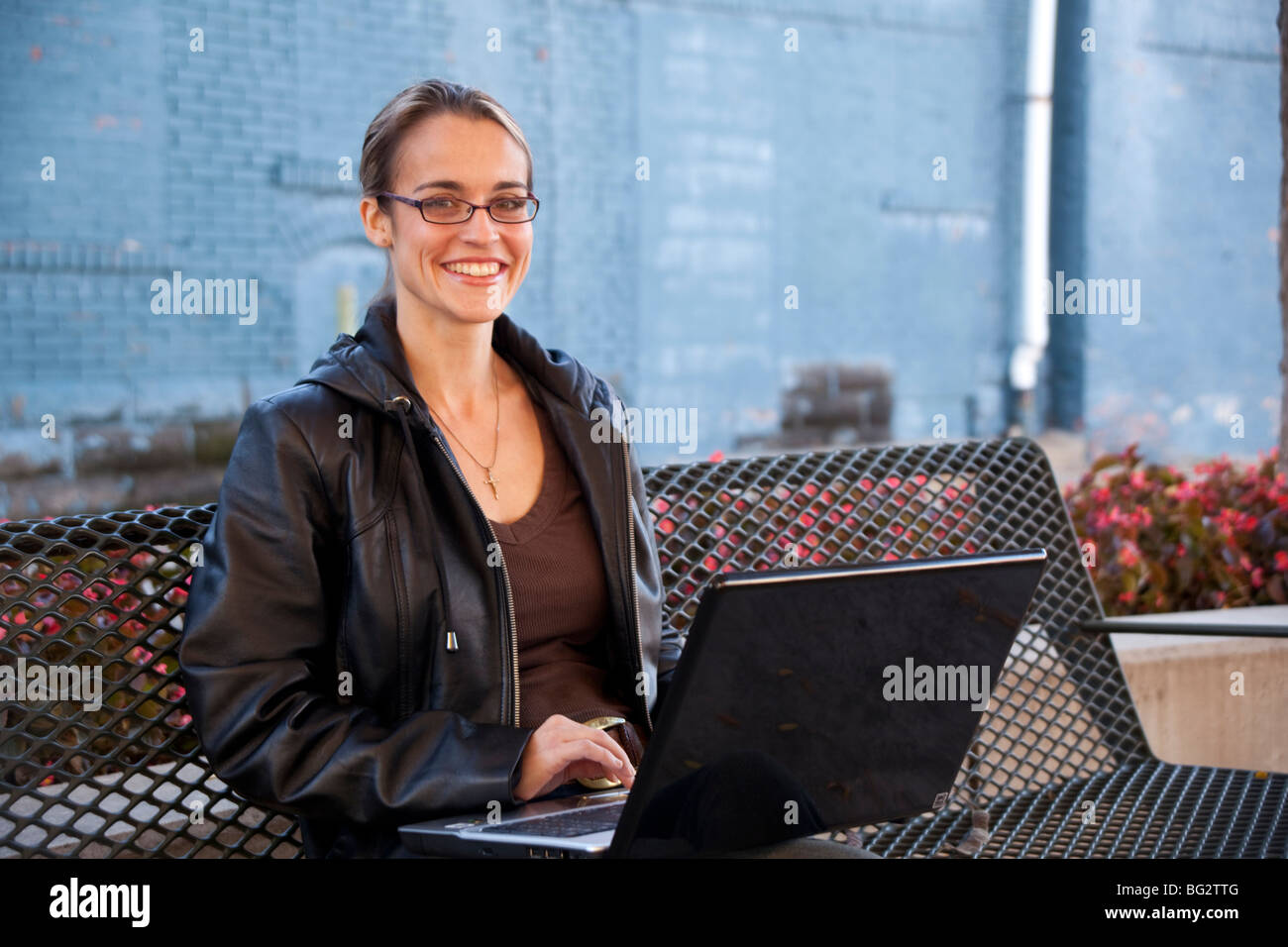 Smiling woman sitting on a parkbench with a notebook computer. Stock Photo