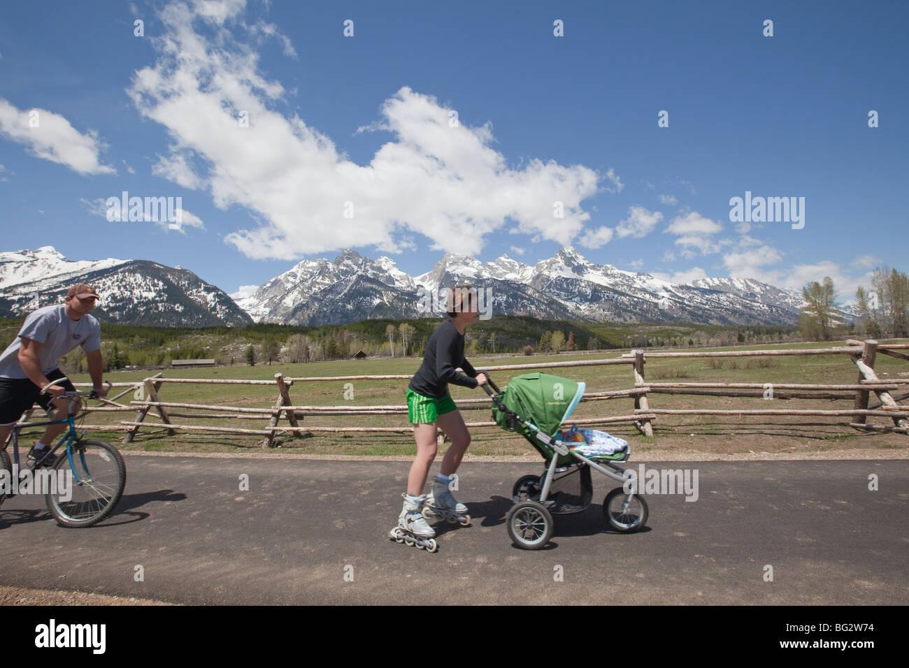 Biker and rollerblading parent  pushing stroller enjoy paved bike trail along Moose-Jenny Lake Road in front of - Stock Image