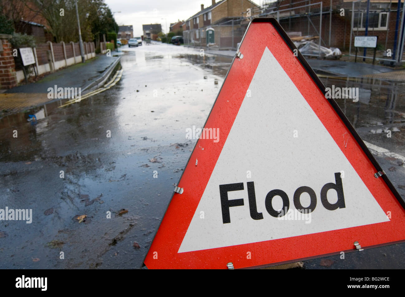flood flooding flooded road roads heavy rain global warming blocked drain drains road sign signs water waters climate - Stock Image