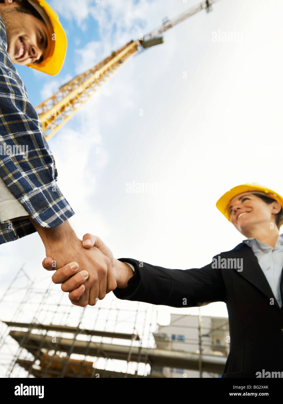 female architect and construction worker shaking hands. Low angle view, copy space - Stock Image