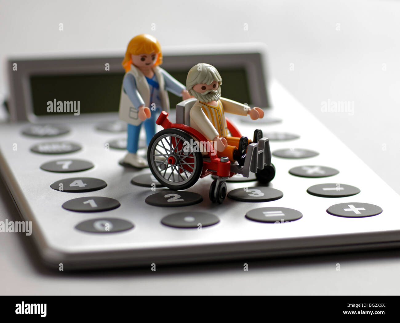 Playmobil toys on a calculater . - Stock Image