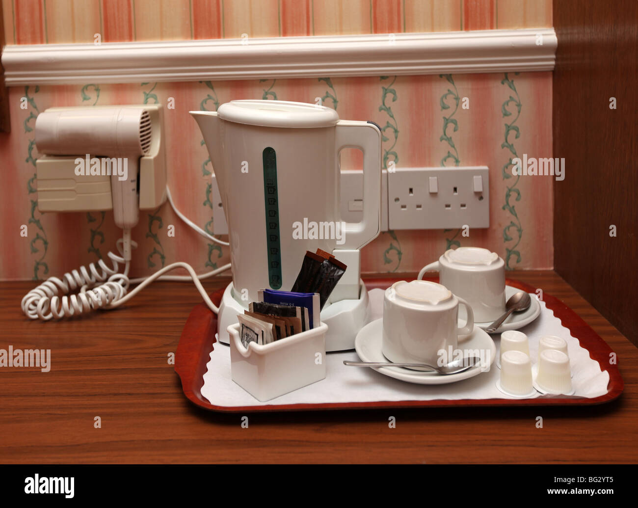 typical uk hotel bedroom accessory - a kettle with cup and saucers