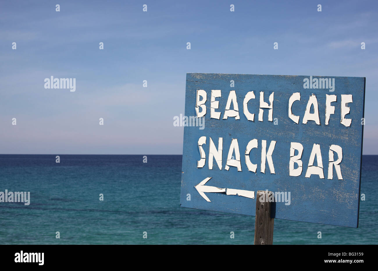 Weather battered sign directing people to a beach cafe and snack bar beside the sea - Stock Image