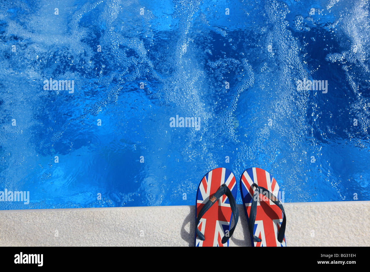 Pair of unbranded flip flops printed with the UK flag or Union Jack placed at the edga of a swimming pool whirlpool - Stock Image