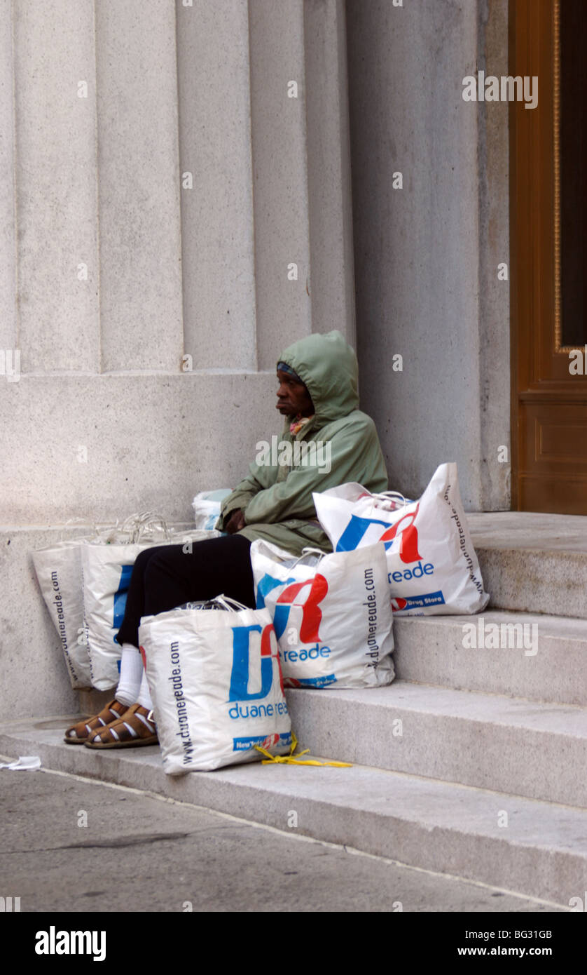 Tramp sitting on steps with bags - Stock Image