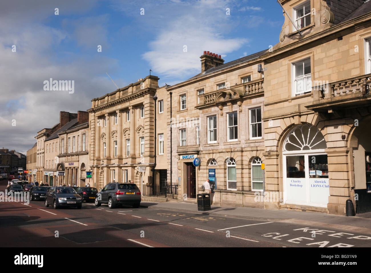 Barclays Lloyds TSB and Halifax Banks with person using Hole in the Wall ATM in Bondgate, Alnwick, Northumberland, - Stock Image