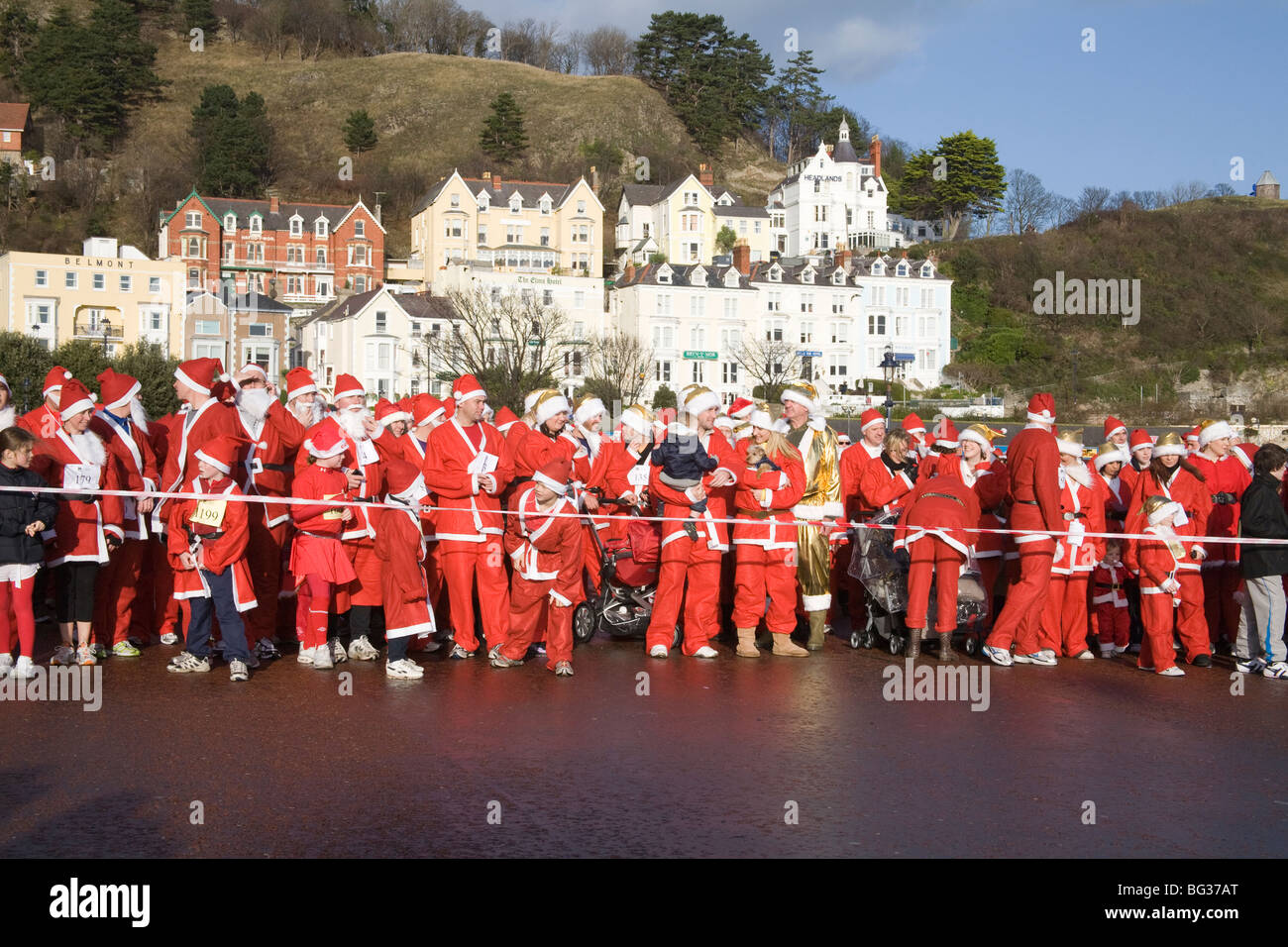 Llandudno North Wales UK December Participants in the annual Santa run for Charity lining up on the promenade raising - Stock Image