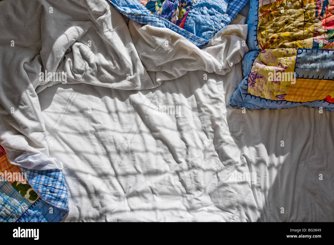 Messy Bed With Wrinkled Sheets And Shadows - Stock Image