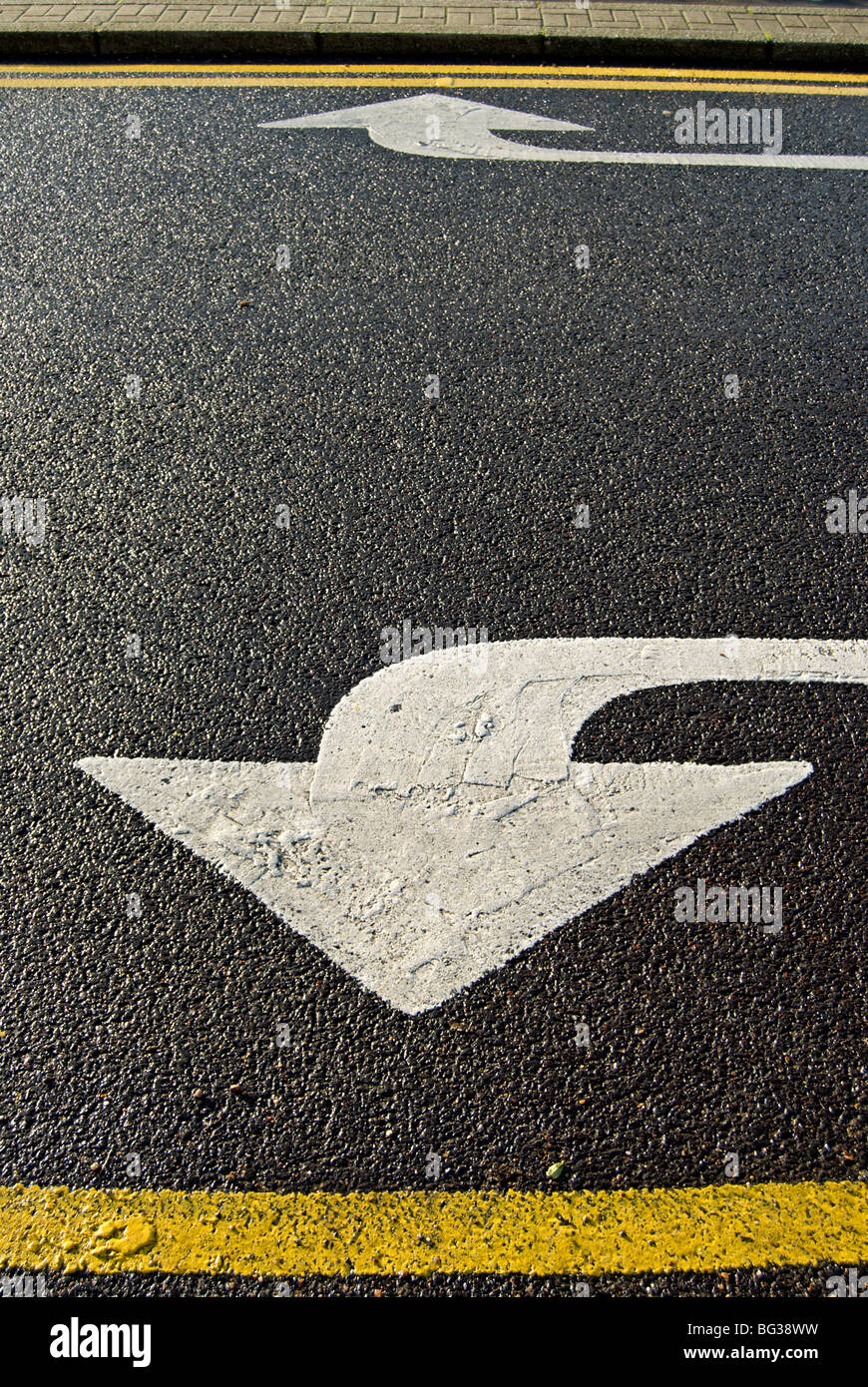 left and right pointing arrows and yellow lines, markings on a british road - Stock Image