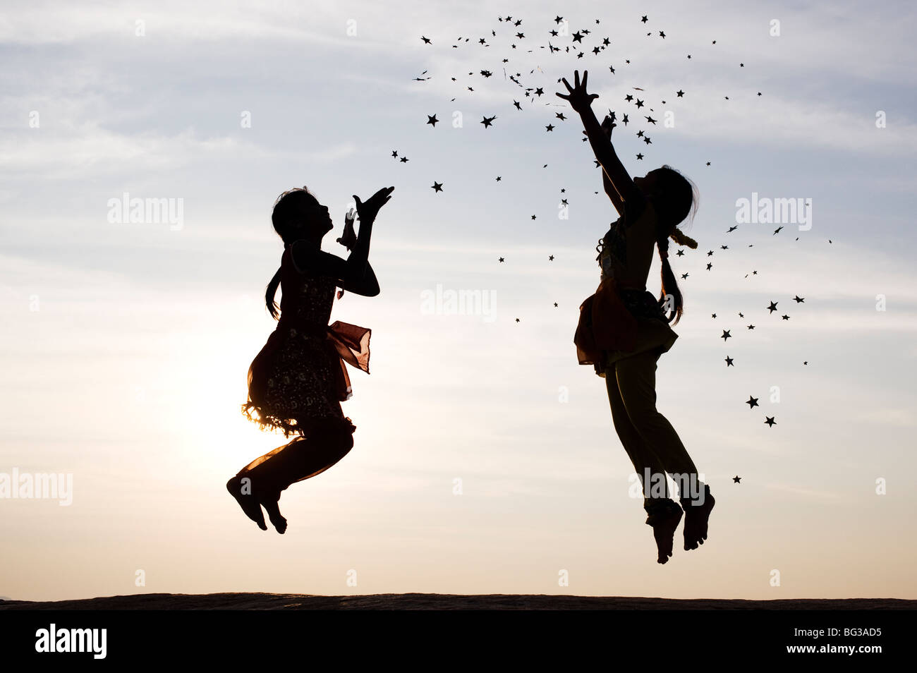 Silhouette of two young Indian girls jumping, throwing and catching stars. India - Stock Image