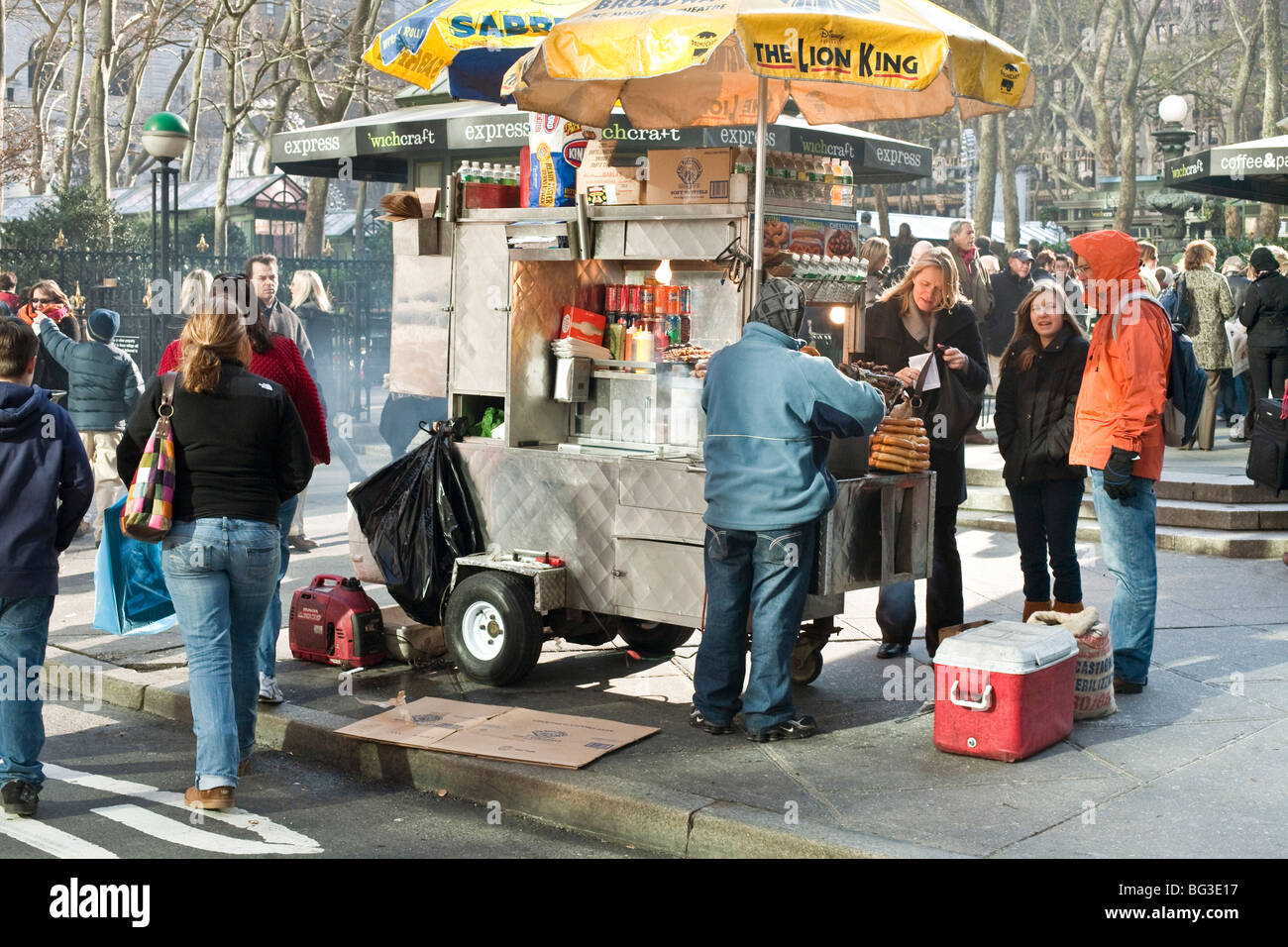 food cart doing a brisk business on 42nd Street outside the corner of Bryant Park on a chilly December Sunday in - Stock Image