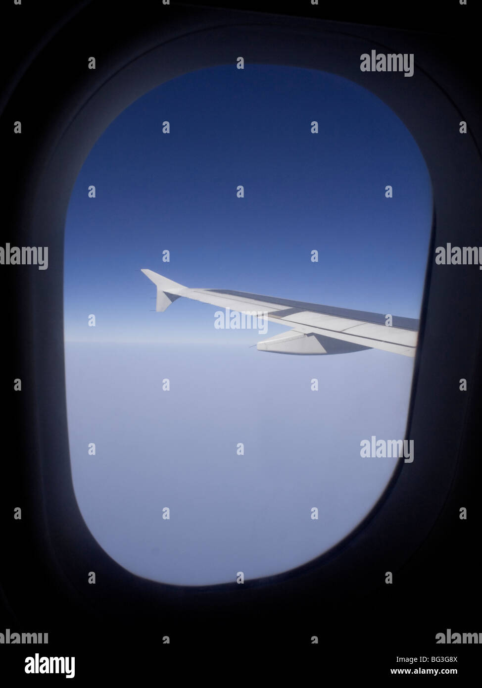 Air travel. View from the cabin window of an Airbus A319 passenger jet in flight, showing the aircraft's wing - Stock Image