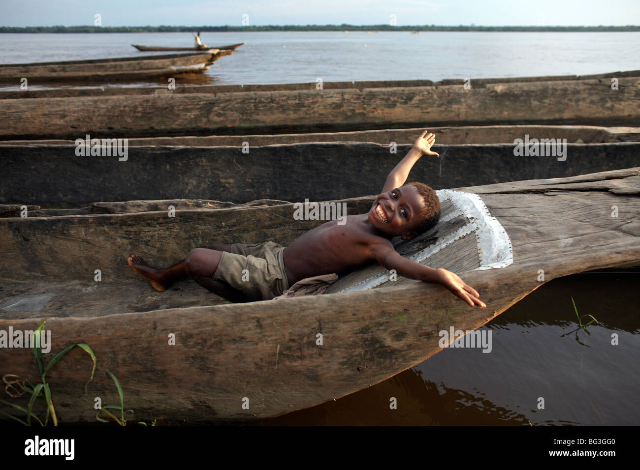 A boy relaxes in a dugout canoe on the Congo River, Yangambi, Democratic Republic of Congo, Africa - Stock Image