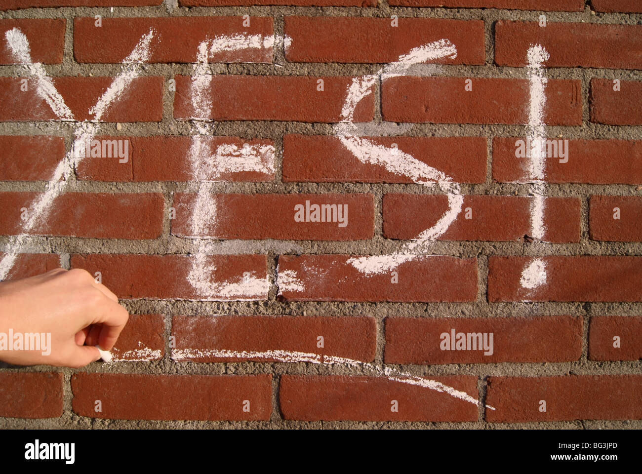 The word 'yes' written on a red rick wall in chalk. - Stock Image