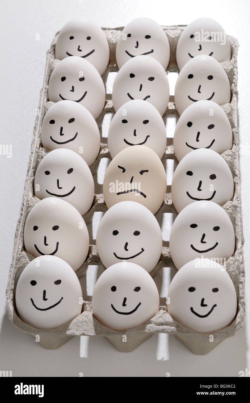 Package of eggs painted with smiling faces except for one grumpy sad mad face - Stock Image