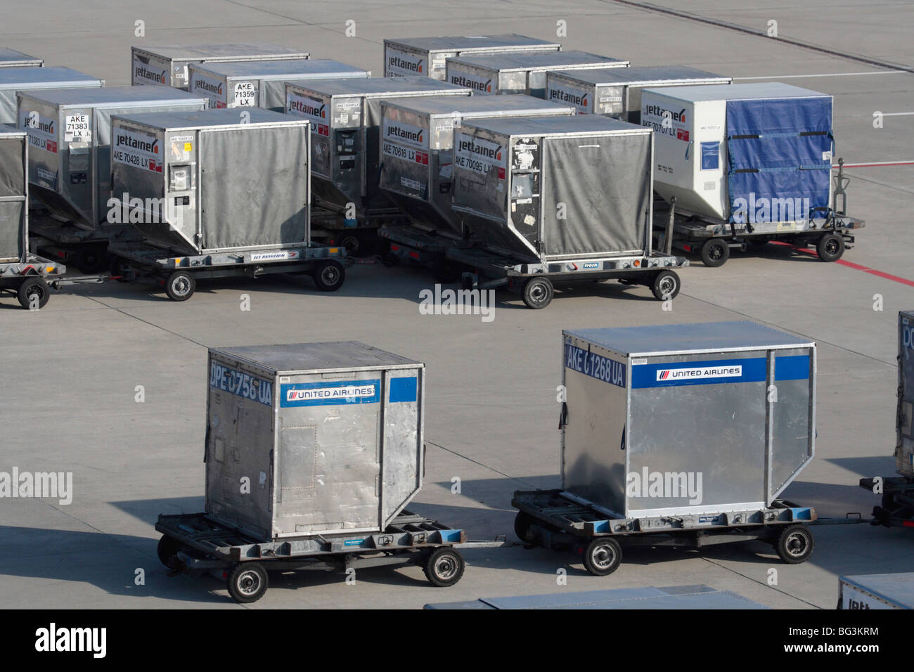 Commercial air freight transport logistics. Air cargo containers on the ramp or apron at an airport waiting for - Stock Image